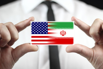 Businessman holding a business card with USA and Iran Flag