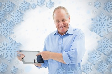 Happy mature man pointing to his tablet pc