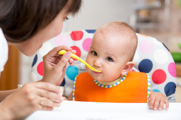 baby eating healthy food on kitchen