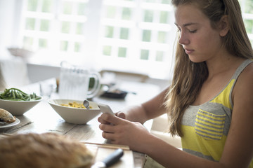 A young girl seated checking her smart phone at a dining table.