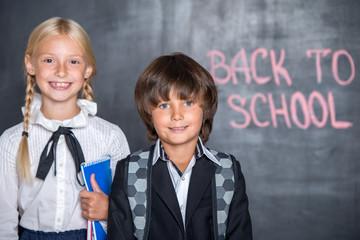 Close-up of little school boy and girl near blackboard