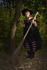 Halloween Witch with Broomstick in the Forest