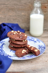 Chocolate and hazelnut cookies with milk, selective focus
