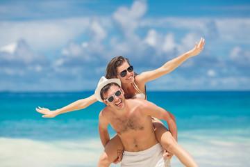 Loving couple having fun on the beach of a tropical ocean.