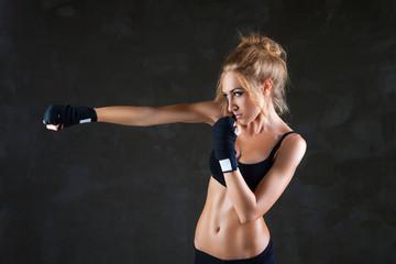 Sexy boxer woman making kick with boxing bandage
