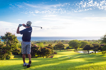 Fotobehang Golf Man hitting golf ball down hill towards ocean and horizon
