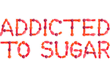 """Phrase """"ADDICTED TO SUGAR"""" made of red sugary candies, isolated"""
