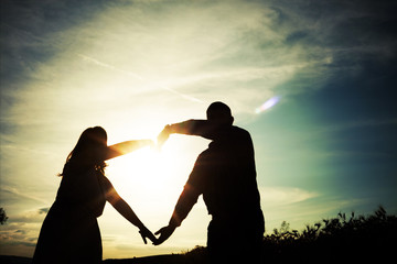 Silhouette of loving couple holding hands in heart shape over or