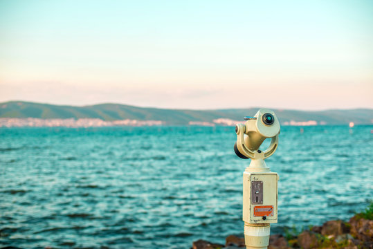 Monocular looking at the evening sea landscape