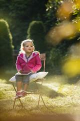 Junges Mädchen sitzt im Garten mit Tablet in Lappe