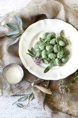 homemade spinach dumplings with sage leafs and flowers