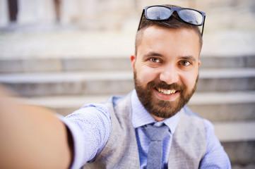 Hipster businessman taking selfie