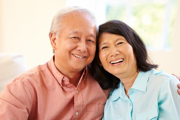 Senior Asian Couple Sitting On Sofa At Home Together