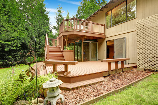 Wooden walkout deck with patio and benches