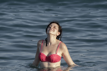 Girl lifted her face the sun, standing waist-deep in water.