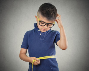 child measuring his waistline isolated on grey background