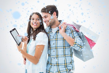 Young couple with shopping bags and tablet pc