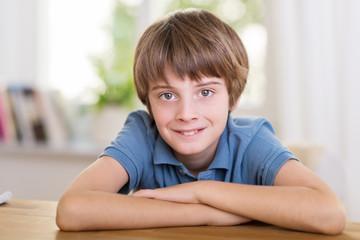 lächelnder junge stützt sich auf tisch