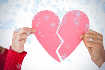 Couple holding two halves of broken heart