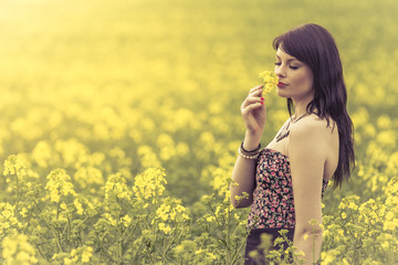 Beautiful woman in meadow of yellow flowers love sniffing flower