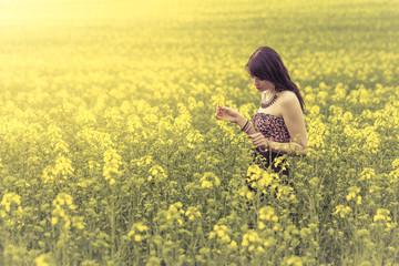 Beautiful woman in meadow of yellow flowers looking down