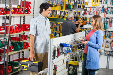 Smiling Couple Buying Tools In Hardware Store