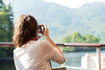 Female enjoying boat ride, taking photos, Scottish Highlands