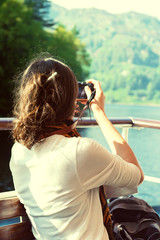 Female enjoying boat ride, taking photos, Scottish Highlands