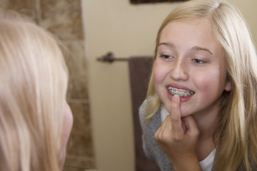 girl looking in the mirror, examining her braces