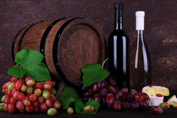 Wine in bottles, Camembert and brie cheese, grapes and wooden