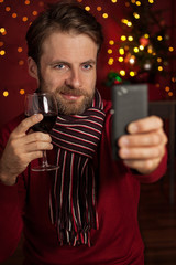 Christmas - man taking photo of himself (selfie) on mobile phone