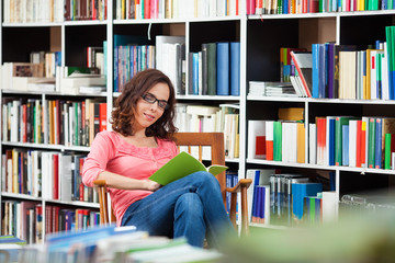 Beautiful young woman enjoying a good book in the library.