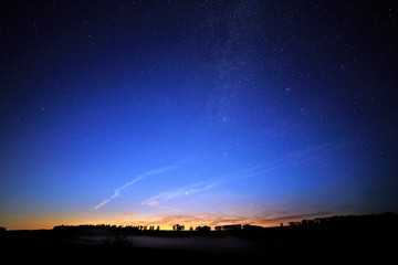 Dawn on a starry background sky and the Milky Way.