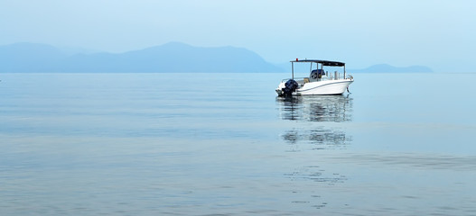 pleasure boat on the background of the islands in the haze