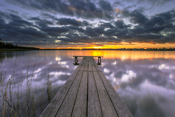 Wall Mural - Purple Sunset over Tranquil Lake with Wooden Jetty