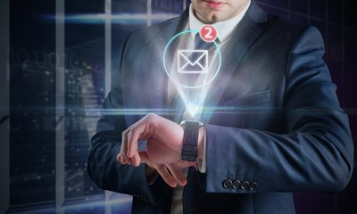 Composite image of businessman using hologram watch