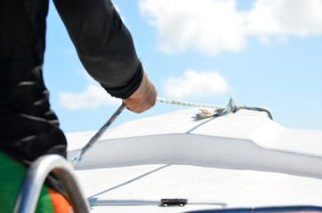 Closeup on man holding rope on the yacht, body part.