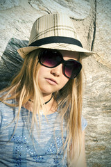 Long-haired girl in hat and sunglasses, portrait