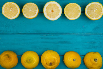 Fresh organic lemons and limes on wooden background