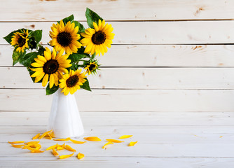 A bouquet of autumn sunflowers in a vase on a wooden table.