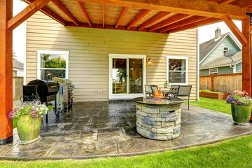 Patio area with tile floor and stone trimmed fire pit