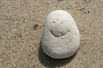 Naturally received image of smile on sea pebble stone on sand