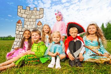 Smiling children in festival costumes sit close