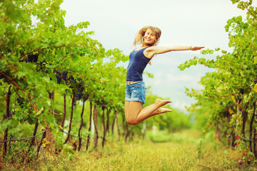 Happy woman in a vineyard in harvest season.