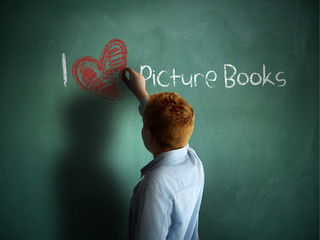 I love Picture Books. Schoolboy writing on a chalkboard.