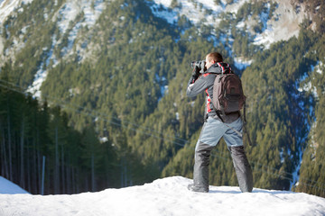 photographer photographing winter panorama in  mountains