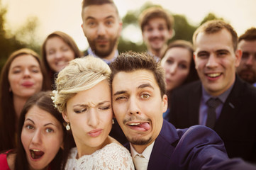 Newlyweds with friends taking selfie