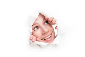 woman peeking through hole torn in white paper