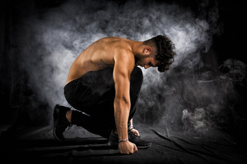 Handsome shirtless muscular young man kneeling down on black