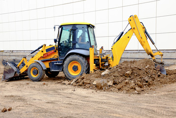 Yellow excavator working with a lot of soil